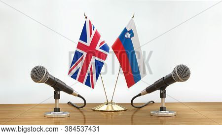 3d Illustration. Microphones And Uk, Sloven Flags Pair On A Desk Over Defocused Background
