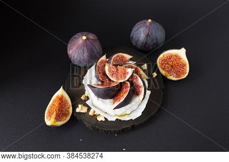 Fresh Figs With Cheese Brie, Walnuts And Honey On Wooden Board Over Black Background. Delicious Appe