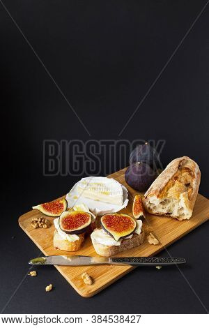 Sandwiches With Cheese Brie, Fresh Figs, Walnuts And Honey On Wooden Board Over Black Background. He