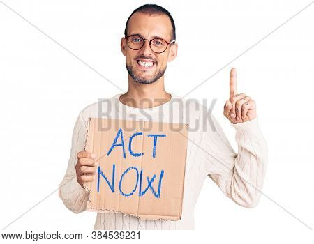 Young handsome man holding act now banner surprised with an idea or question pointing finger with happy face, number one