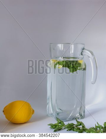 Pure Water With Lemon And Mint In A Transparent Glass Jug. Yellow Lemon And Green Branch Nearby. Gra