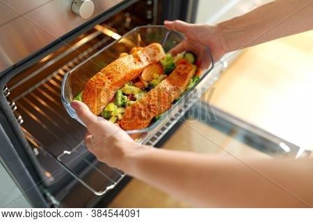 culinary, food and people concept - woman cooking salmon fish with vegetables in baking dish in oven at home kitchen