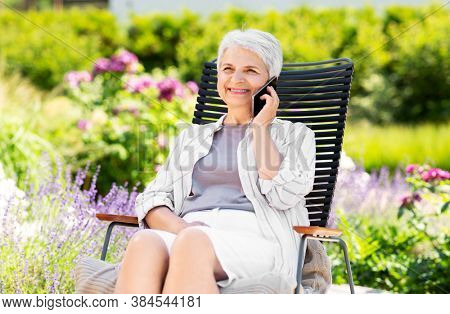 technology, old age and people concept - happy smiling senior woman calling on smartphone resting at summer garden