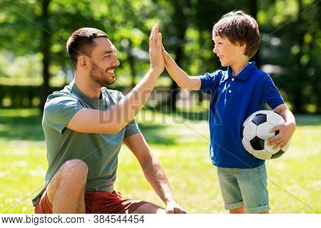 family, fatherhood and people concept - happy father and little son with soccer ball making high five gesture at summer park