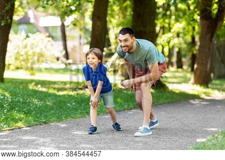 family, fatherhood and people concept - happy father and little son compete in running at summer park