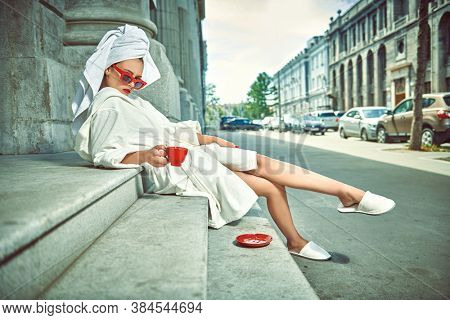 Glamorous lifestyle. Stunning woman in a white terry dressing gown with a white towel on her head and elegant sunglasses alluring on a city street with a cup of tea. Fashion shot.