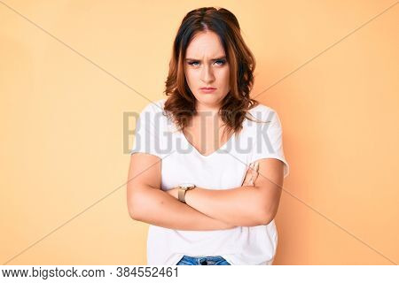 Young beautiful caucasian woman wearing casual white tshirt skeptic and nervous, disapproving expression on face with crossed arms. negative person.