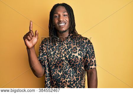 African american man with braids wearing leopard animal print shirt pointing finger up with successful idea. exited and happy. number one.