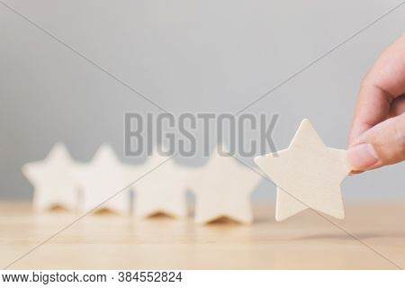 Hand Putting Wooden Five Star Shape On Wood Table. The Best Excellent Business Services Rating Custo