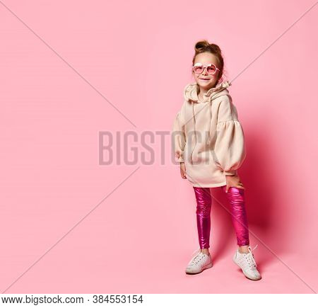 Little Girl In Stylish Pink Clothes And Round Glasses Posing Leaning Forward. Full Length Shot Isola