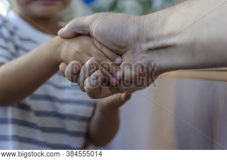 A Child And An Adult Shake Hands Indoors. Friendship, Happy Time. Selective Focus.