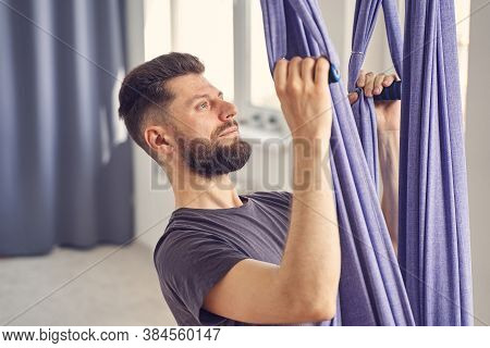 Handsome Young Man Using Blue Hammock Swing For Aerial Yoga