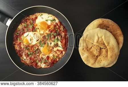 Shakshuka - Poached Eggs In Tomato Sauce, Onion, Pepper And In Iron Pan With Pita Bread On Dark Wood