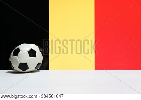 Small Football On The White Floor With Black Yelow And Red Color Of Belgian Nation Flag Background.