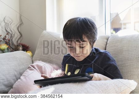 High Key Kid Sitting On Sofa Watching Cartoon On Tablet,happy Boy Playing Game On Touch Pad With Bri