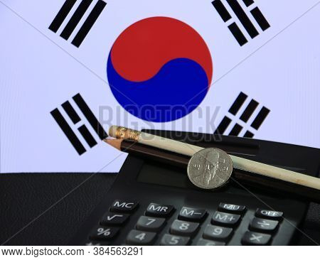 One Hundred Korean Won Coin On Obverse, (krw) On Black Calculator With Black And White Pencil On Bla