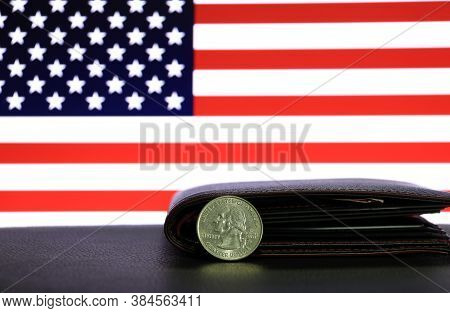 A Quarter Of Us Dollar Coins On Obverse (usd) And Black Wallet On Black Floor With American Flag Bac