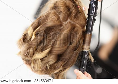 Hairdresser Makes Curls On Womens Hair With Curling Iron. Beauty Salon Services Concept