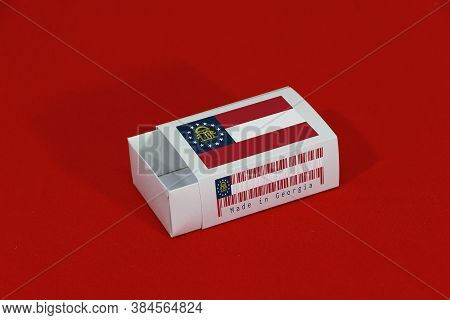 Georgia Flag On White Box With Barcode And The Color Of State Flag On Red Background, Paper Packagin