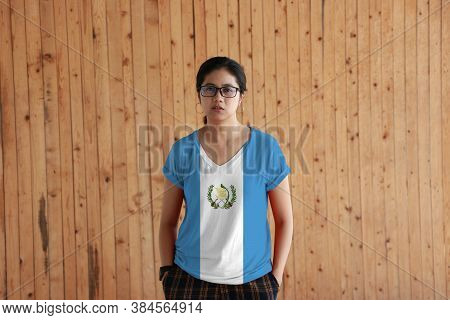 Woman Wearing Guatemala Flag Color Shirt And Standing With Two Hands In Pant Pockets On The Wooden W