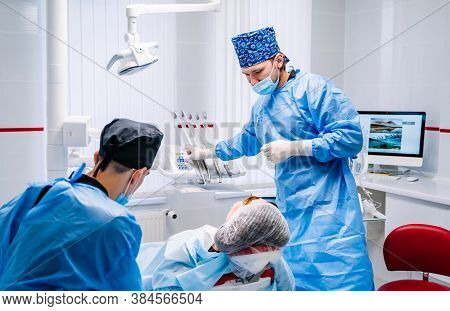 Male Dentist Is Working In Modern Stomatology Clinic. Stomatological Instrument In The Dentist Clini