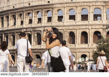 Rome, Italy - June 27, 2010: A Young Girl Takes Pictures Of Tourists And Via Dei Fori Imperiali, Wit