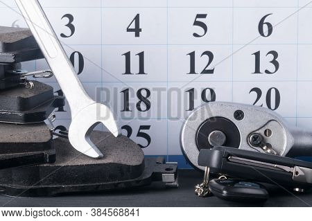 Background Of A Set Of Spare Parts Items And A Calendar, Brake Pads And Spanners