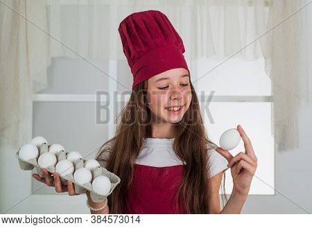 Preparing From Eggs. Happy Child Wear Cook Uniform. Chef Girl In Hat And Apron. Kid Cooking Food In