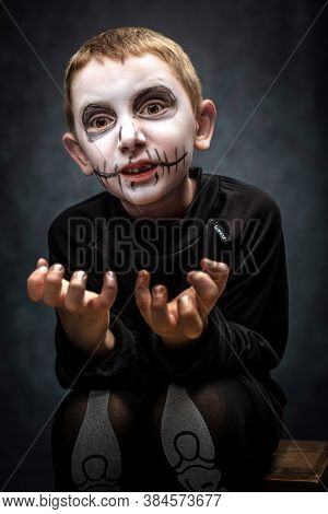 child dressed as skeleton in scary pose. halloween costume, studio shot