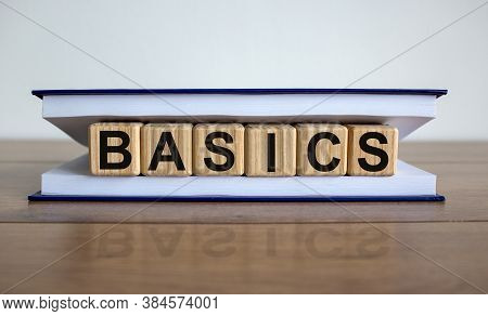 Concept Word 'basics' On Wooden Cubes Between Pages Of A Book On A Beautiful Wooden Table. White Bac