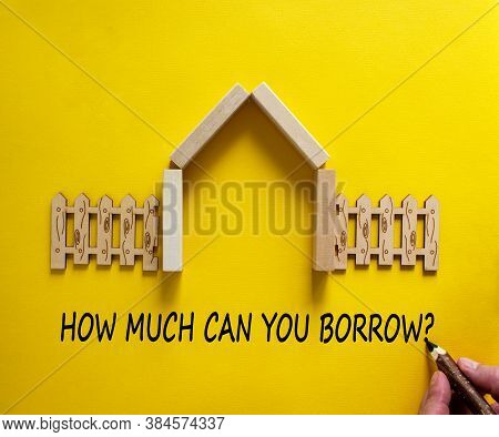 Hand Writing 'how Much Can You Borrow' On Beautiful Yellow Background. Model Of A Wooden House. Male