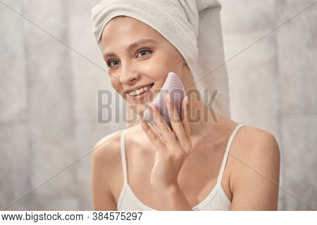 Lady Using A Sonic Facial Cleansing Brush