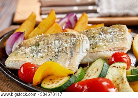 fish with grilled vegetables on the pan