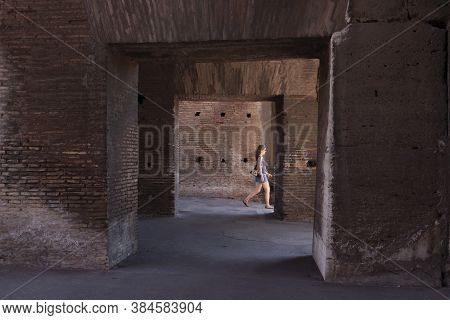 Rome, Italy - June 29, 2010: A Tourist Woman Walks, Looking For The Exit, Between The Corridors, Arc