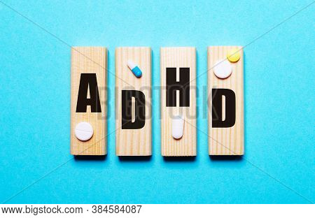 Attention Deficit Hyperactivity Disorder Adhd Written On Wooden Blocks On A Blue Background. Medical