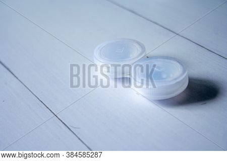 Containers For Contact Lenses On Wooden Table Background.