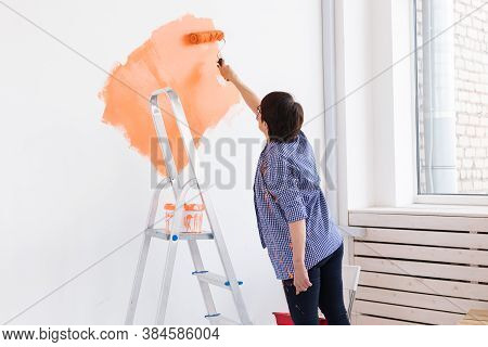 Middle-aged Woman Painting The Walls Of New Home. Renovation, Repair And Redecoration Concept.