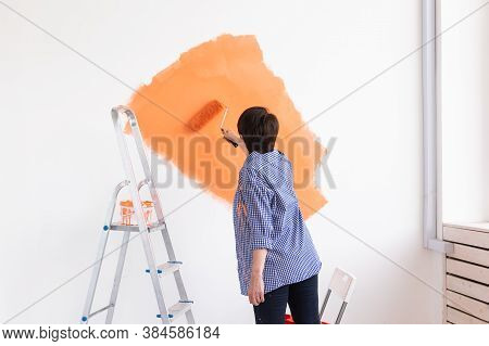 Beautiful Middle-aged Woman Painting Wall In Her New Apartment. Renovation And Redecoration Concept.