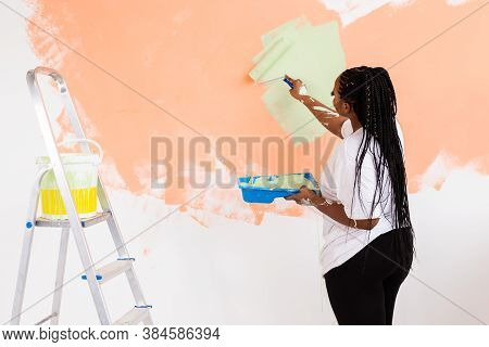 Young Beautiful African American Woman Painting Wall In Her New Apartment. Renovation And Redecorati