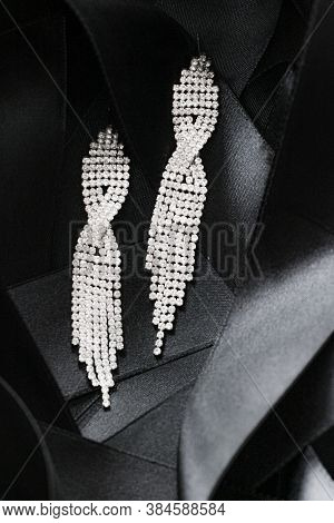 Luxury Diamond Earrings On Black Silk Ribbon As Background, Jewelry And Fashion Brand