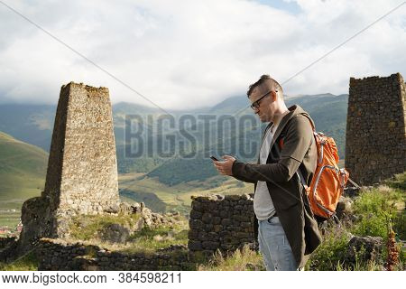 Young Man With Backpack And Smartphone Stands Near Old Towers On Background Of Mighty Mountains. Mal