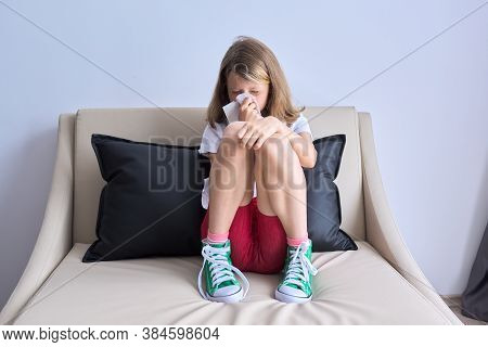Girl Child Sneezing In A Handkerchief Sitting At Home On The Couch, Cold Season