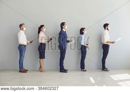 Job Seekers Wearing Face Masks Standing In Row Keeping Safe Distance While Waiting For Job Interview