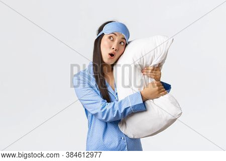 Surprised Asian Girl In Awe Wearing Sleeping Mask And Pajamas As Lying In Bed And Hugging Pillow, Lo