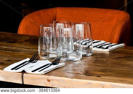 Table On Restaurant, Served For Four: Glasses, Napkins And Cutlery On Wooden Table And The Orange Ba