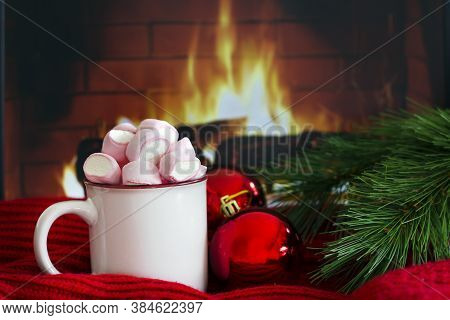 Cozy Scene Near Fireplace With A White Enameled Mug With Hot Drink With Marshmallow Next To Red Chri