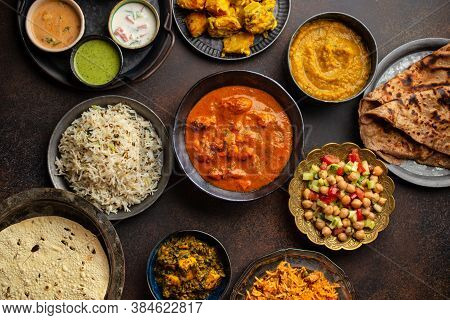 Variety Of Indian Food, Different Dishes And Snacks On Dark Rustic Background. Pilaf, Butter Chicken