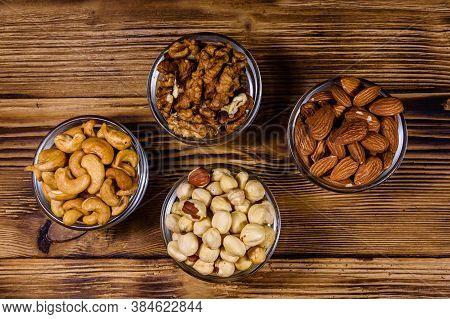 Various Nuts (almond, Cashew, Hazelnut, Walnut) In Glass Bowls On Wooden Table. Vegetarian Meal. Hea