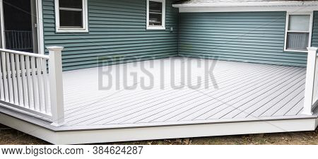 A Composite Dick Is Buiilt On To The Back Of A House That Has Green Vinyl Siding.
