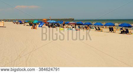 Myrtle Beach Sc - June 22, 2020 - Summertime Beachgoers Under Blue Umbrellas On June 22, 2020 In Myr